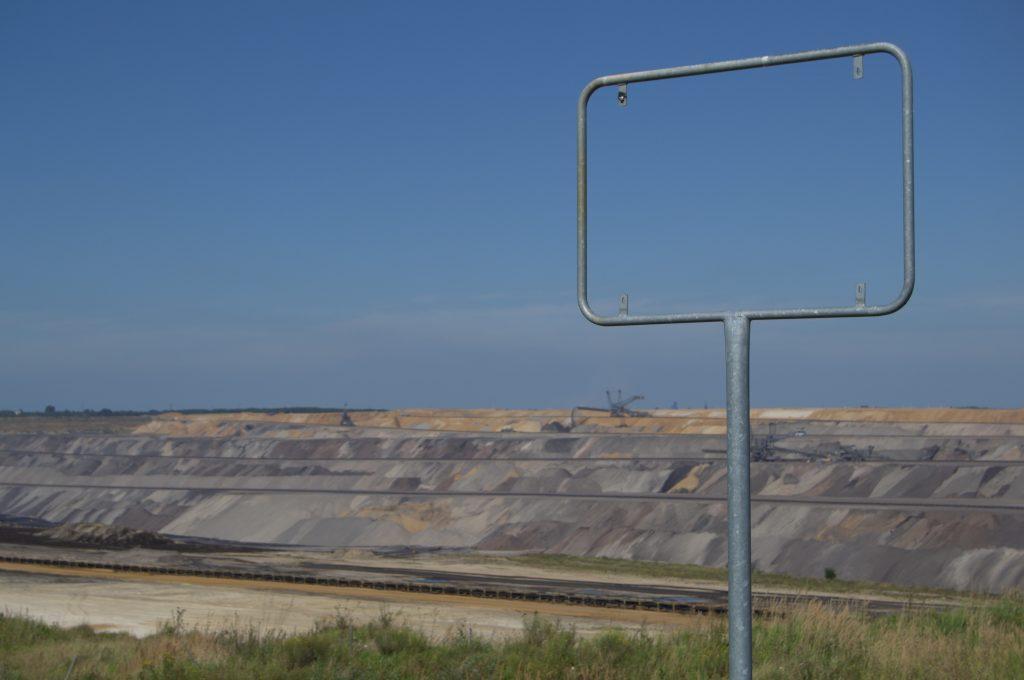 """Leeres Ortsschild rahmt den Blick auf den Tagebau Garzweiler (am """"Skywalk"""")"""